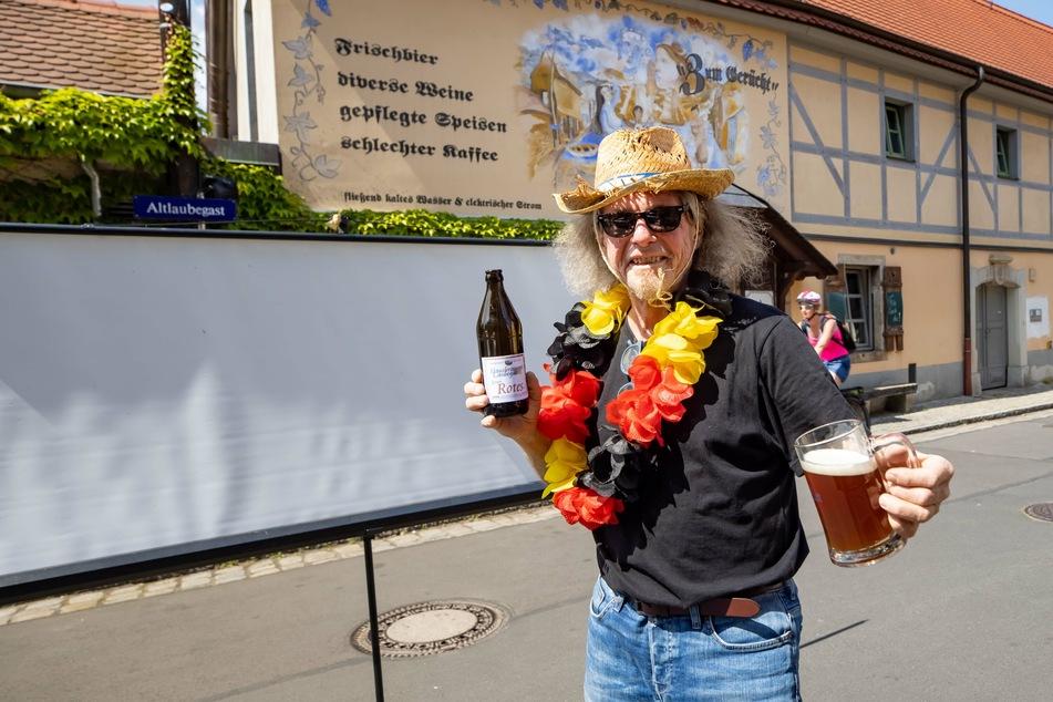 """Matteo Böhmes Vater Thomas (60) steht im Fan-Outfit mit Frischgezapftem vor dem kleinen Lokal """"Zum Gerücht"""" und der aufgebauten Leinwand."""
