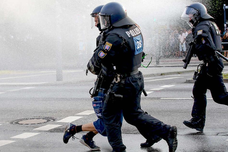 Polizisten nehmen am Pferdemarkt in Hamburg eine Person während eines Wasserwerfereinsatzes in Gewahrsam.