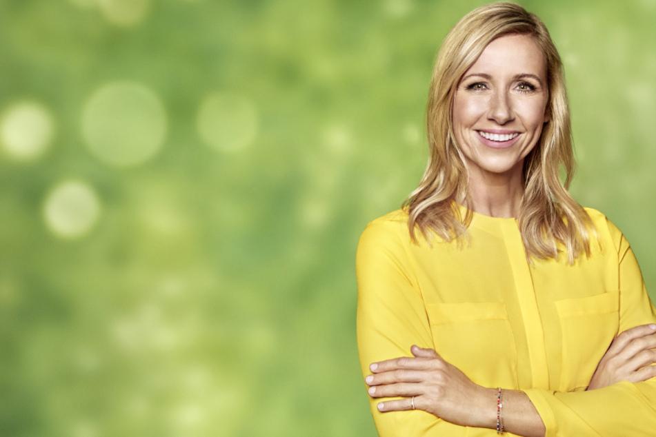 """""""Fernsehgarten""""-Moderatorin Andrea Kiewel steht in einer gelben Bluse vor grünem Hintergrund."""