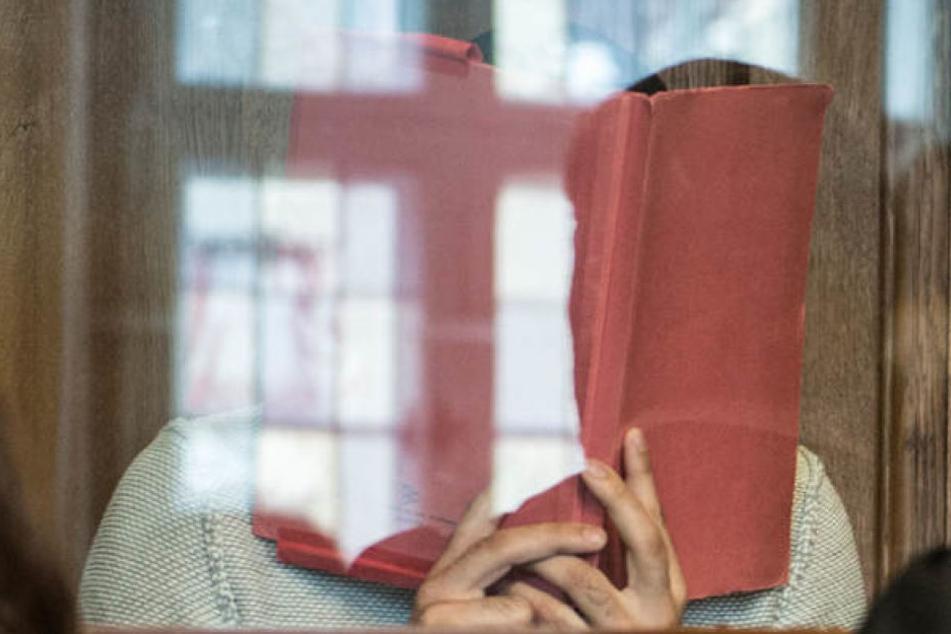 Der Angeklagte versteckt sein Gesicht hinter einem Ordner.