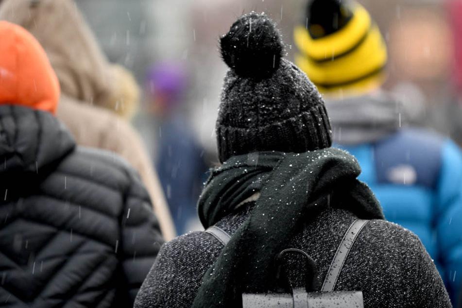 Schneeregen fällt auf Spaziergänger.