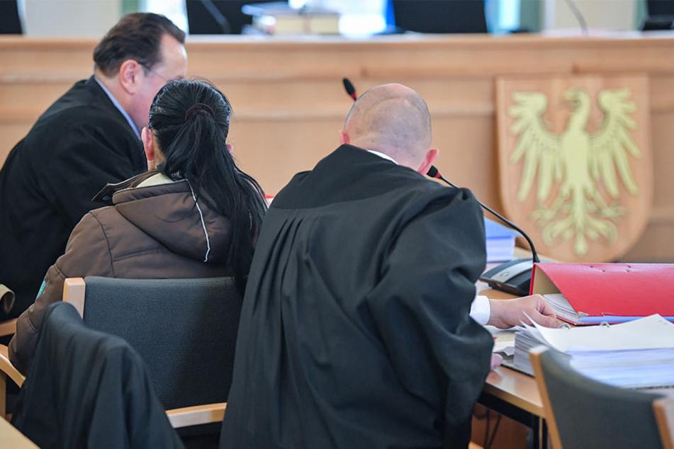 Die Angeklagte sitzt in einem Verhandlungssaal des Landgerichts zwischen Anwälten.