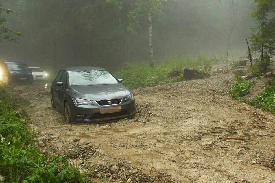 Nach heftigen Gewittern steht ein Auto in einer Mure mit Geröll und Schlamm im Bereich Kaiserbachtal.