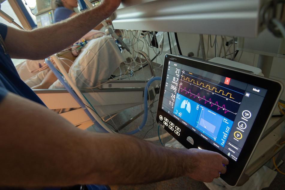 Ein Arzt bedient eine Beatmungsmaschine auf einer Intensivstation.