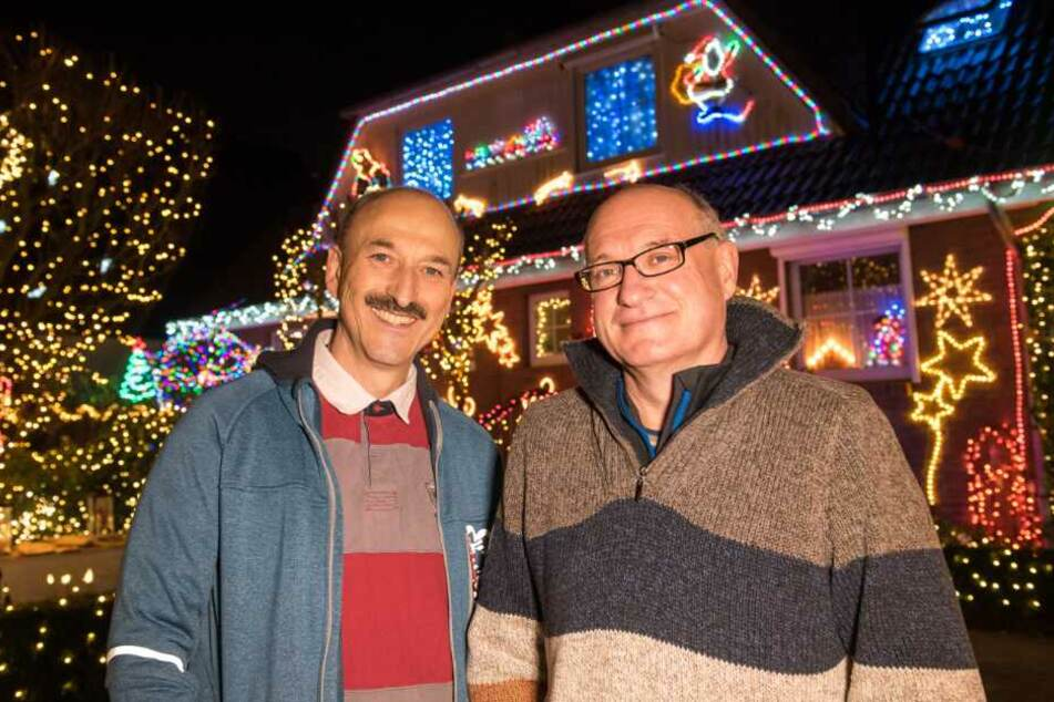 Die Nachbarn Stephan Kalkreuter (l) und Uwe Farkas stehen vor ihrem weihnachtlich geschmückten Haus.