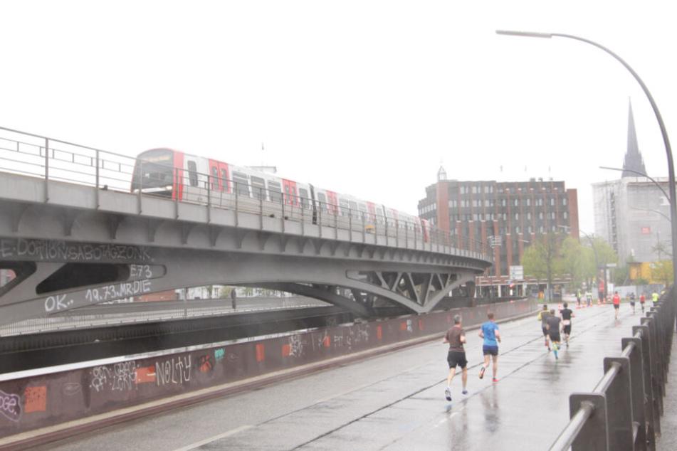 Neben der Linie U3 am Baumwall kämpfen sich die Läufer durch den Regen.