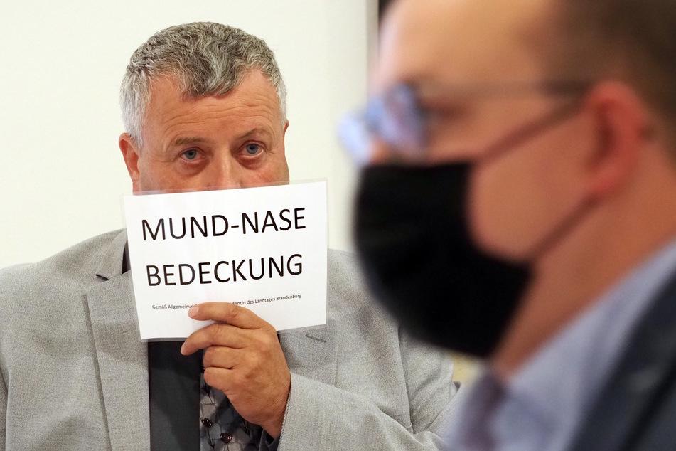 """Michael Hanko (AfD) hält sich während der Landtagssitzung ein Schild mit dem Aufdruck """"Mund-Nase-Bedeckung"""" vors Gesicht."""