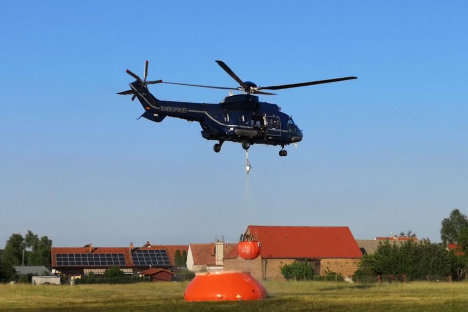 Ein Hubschrauber der Bundespolizei nimmt mit einem Löschwasser-Außenlastbehälter nahe Jüterbog Wasser auf.