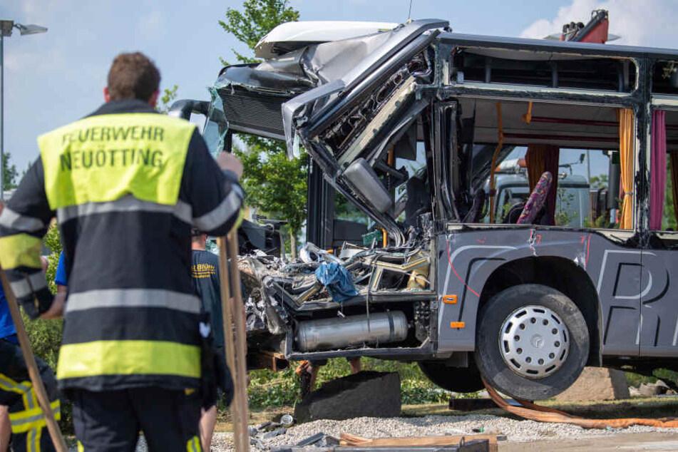 Ein Feuerwehrmann steht vor einem durch einen Unfall völlig zerstörten Schulbus.