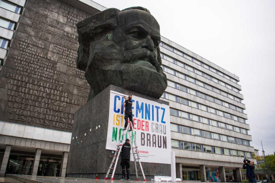 """Zwei Männer befestigen am Karl-Marx-Denkmal ein Plakat mit der Aufschrift """"Chemnitz ist weder grau noch braun"""". (Archivfoto)"""