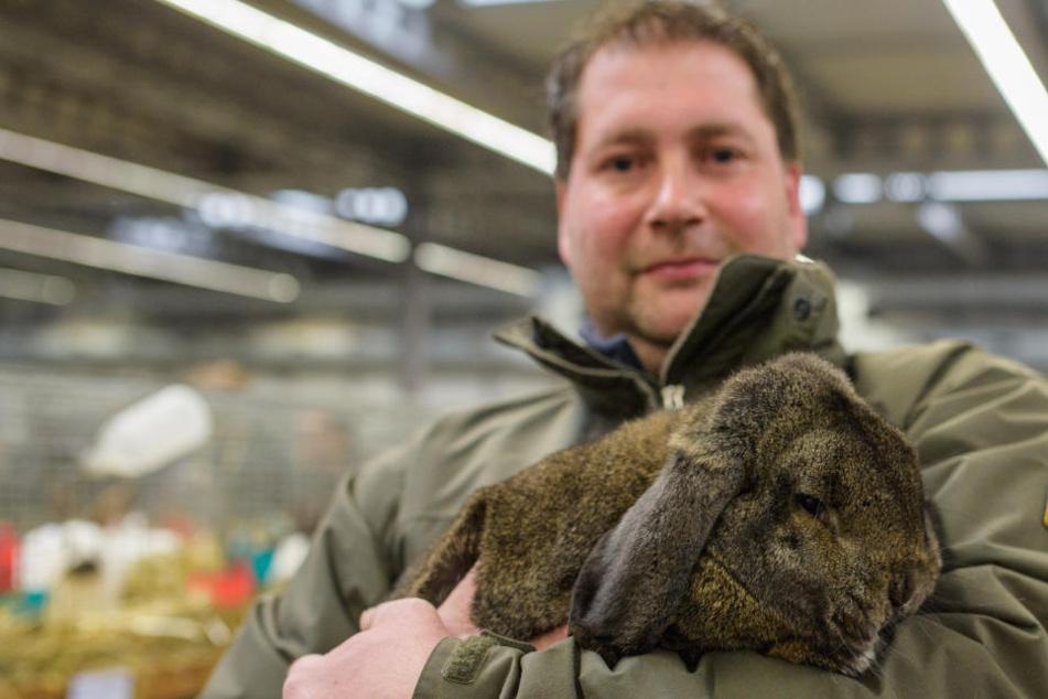 """Thomas Dierksen aus Weener (Ostfriesland) hält sein Kaninchen der Rasse """"Deutscher Kleinwidder"""" auf dem Arm, das als Bundessieger der Rasse ausgezeichnet wurde."""