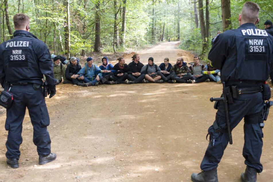 Polizisten beobachten eine Sitzblockade im Hambacher Forst.