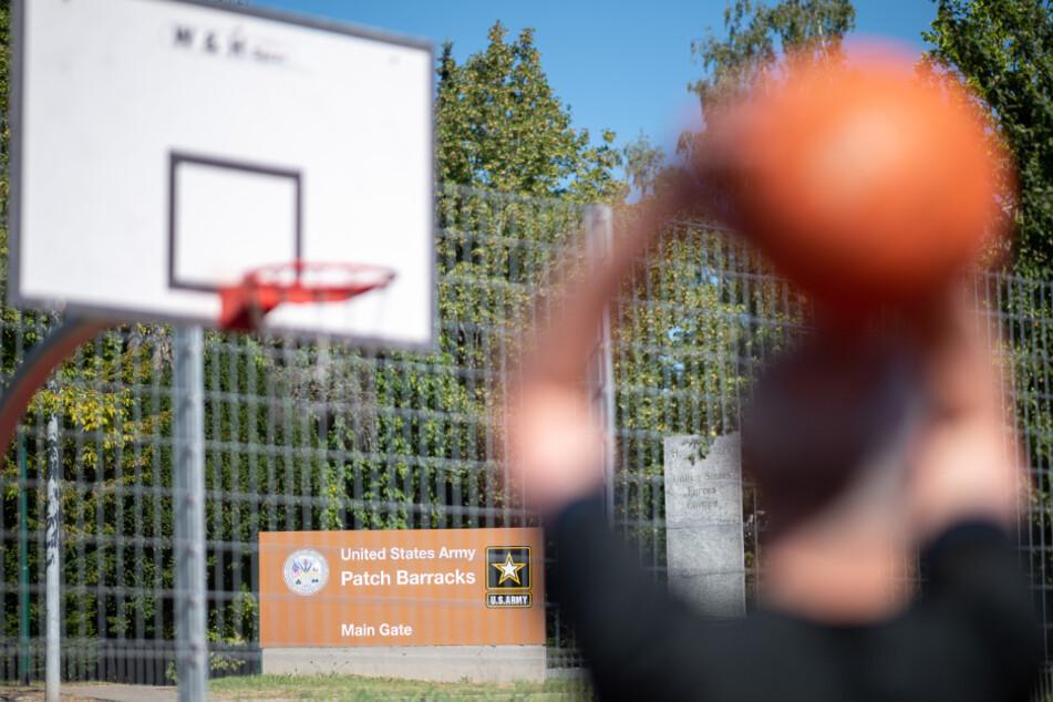"""Ein Mann spielt vor einem Schild, das auf den Haupteingang der US-Kaserne """"Patch Barracks"""" hinweist, Basketball."""