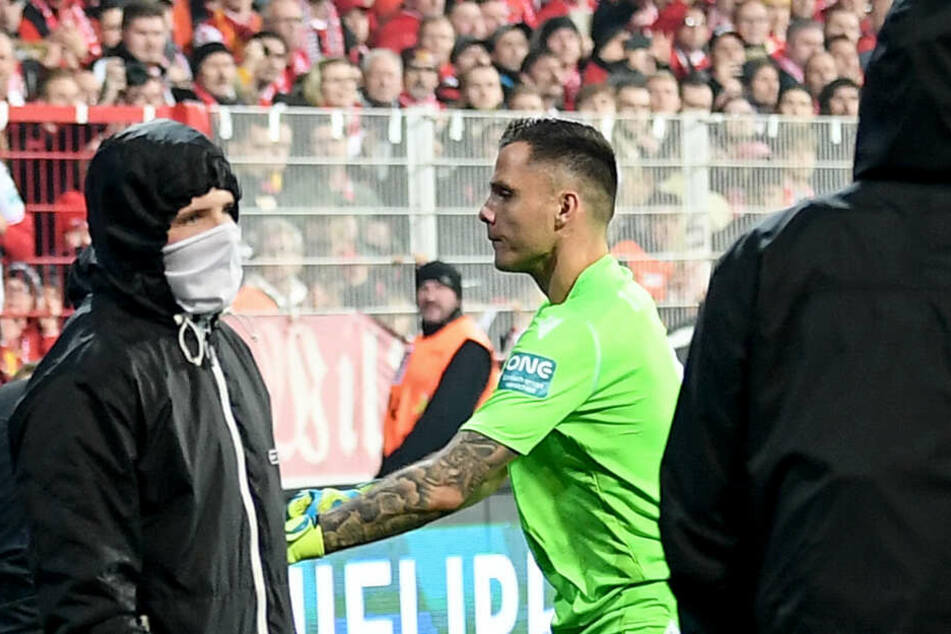 Unions Rafal Gikiewicz (M) beruhigt vermummte Fans seines Vereins, nachdem Hertha-Fans Pyrotechnik auf das Spielfeld geschossen (Symbolbild).