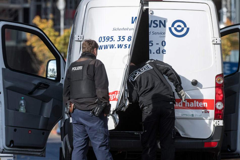 Polizeibeamte stehen an einem Geldtransporter mit aufgebrochenen Türen. (Archivbild)