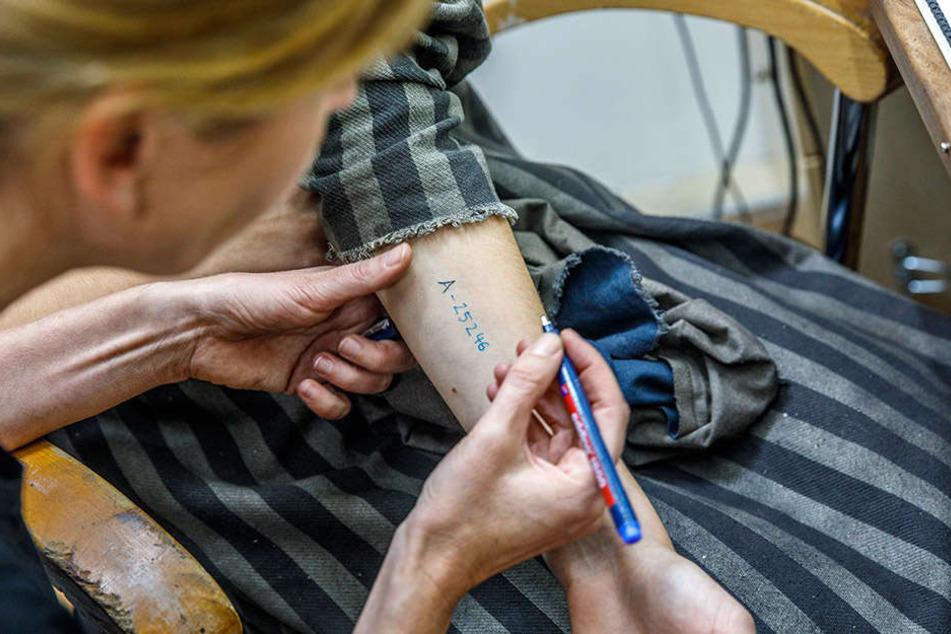 Mit einem haltbaren Stift schreibt die Maskenbildnerin den Schauspielern die  KZ-Nummer auf den Unterarm.