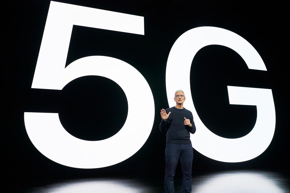 Tim Cook, Chef (CEO) von Apple, vor einem 5G-Schriftzug.