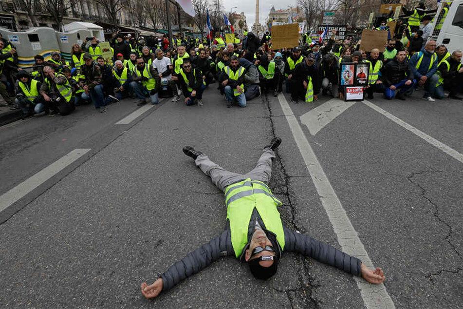 """Ein Demonstrant liegt bei einem Protest der """"Gelbwesten"""" in Marseille auf einer Straße."""