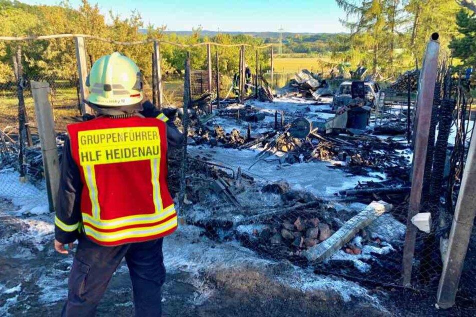 Der riesige Carport, ein Auto, eine Simson, ein Rasenmäher: Ein Feuerwehrmann steht vor jeder Menge Schrott, vernichtet durch den Brand.