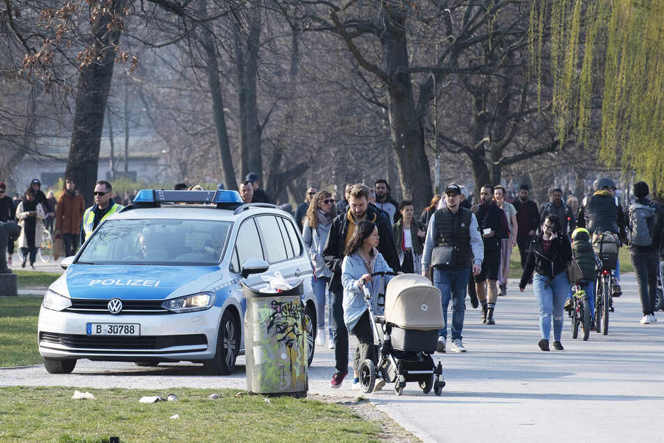 Eine Polizeistreife fährt durch den Treptower Park und fordert die Menschen auf, die Wiese zu verlassen. Aufgrund des Coranavirus ist es verboten, sich länger in Parks und Grünauflagen aufzuhalten, ohne sich zu bewegen.