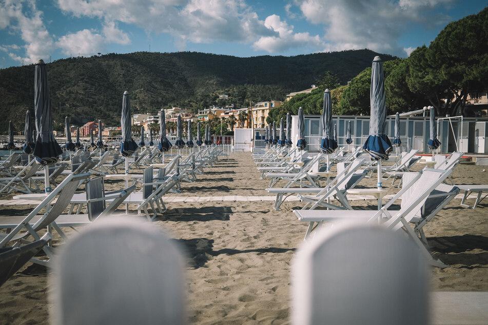 Liegestühle und Sonnenschirme stehen an einem Strand. Die Wiederaufnahme des Personenverkehrs zwischen den italienischen Regionen soll am 3. Juni uneingeschränkt wieder möglich sein. Darauf bereiten sich die touristische Region in und um Genua vor.