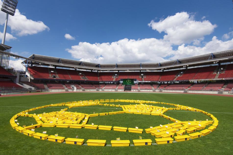 Künstler haben 350 gelbe Blumenkästen auf dem Rasen des Max-Morlock-Stadions zu einem Kunstwerk in Form eines Fußballs aufgebaut.