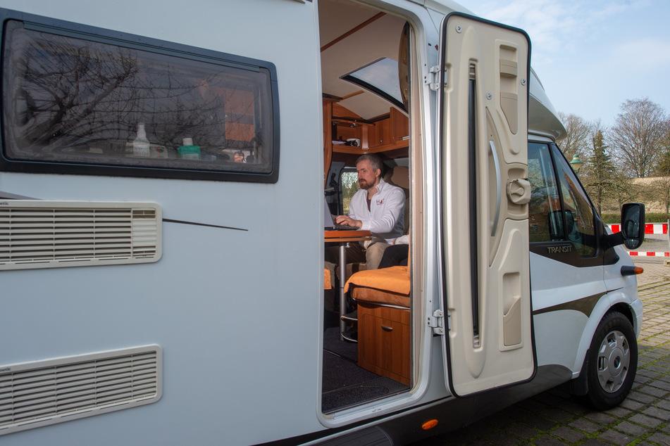 """Der Arzt Robin John sitzt in einem Wohnmobil und spricht via Sprechanlage mit Besuchern des """"Corona-Drive-in""""."""