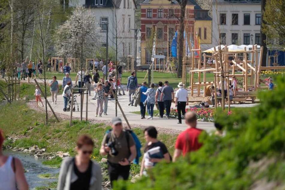 Besucher der sächsischen Landesgartenschau gehen über das Ausstellungsgelände am Mühlbach.