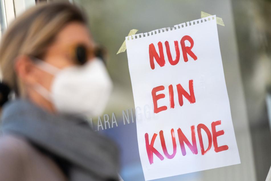 Mit Mund-Nasen-Schutz geht eine Frau an einem Geschäft vorbei.