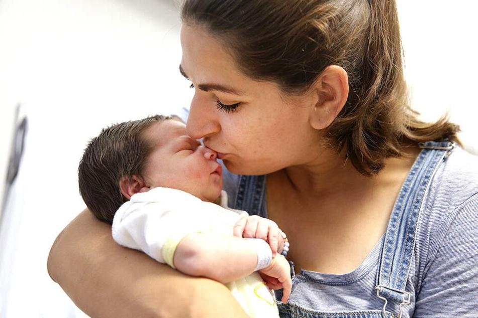 Mama Cindy Mathieu gibt ihrem Kind einen zarten Kuss.