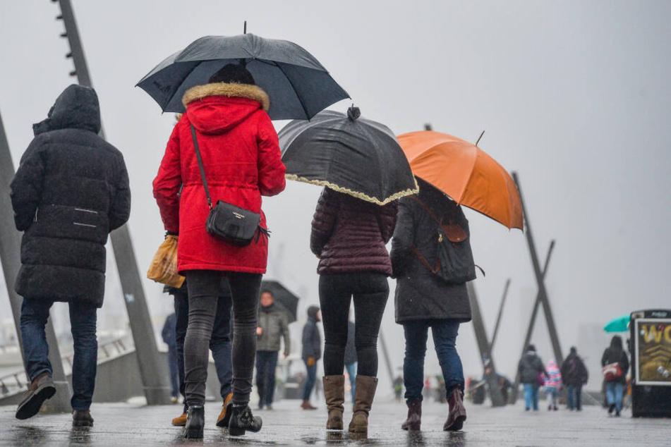 Passanten gehen bei Regen und Kälte über die Landungsbrücken am Hamburger Hafen.