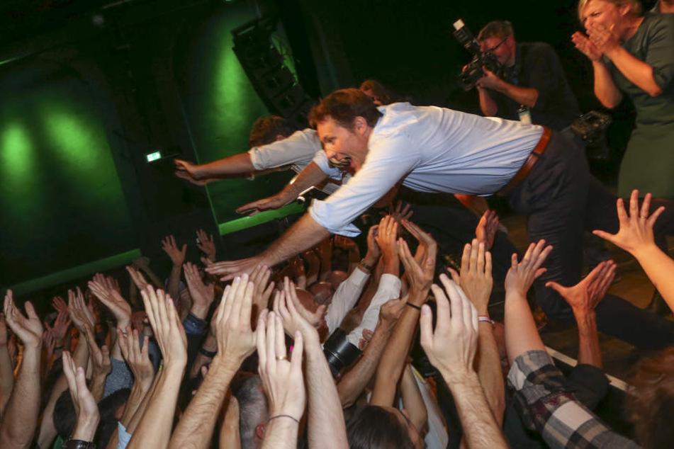 Der Bundesvorsitzende Robert Habeck (l) und der bayerische Spitzenkandidat von Bündnis 90/Die Grünen, Ludwig Hartmann springen bei der Wahlparty der Partei von der Bühne ins Publikum.