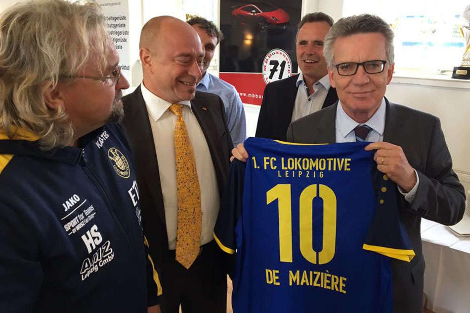 Stolz hält der Bundesinnenminister sein blau-gelbes Trikot in die Kamera.