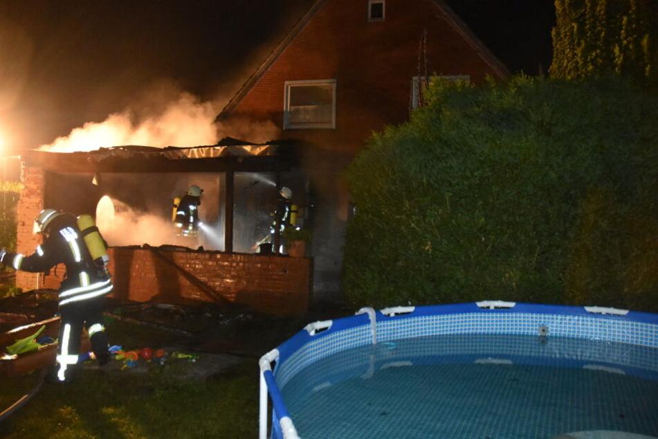 Feuerwehrleute versuchen den Wohnhausbrand in Fredenbeck einzudämmen.