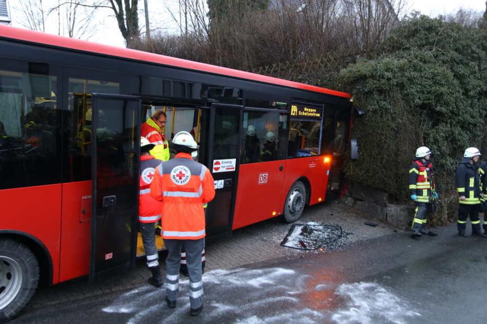 Ein Schulbus steht nach einem Unfall vor einer Mauer.