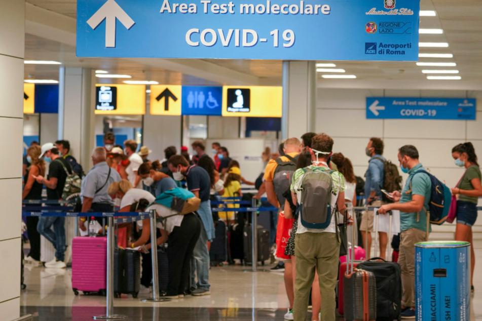 Rom: Urlauber stehen im Flughafen in einer Schlange für einen Covid-19-Test. Für alle Reisende, die aus Kroatien, Griechenland, Malta oder Spanien nach Italien einreisen, ist ein Covid-19-Test obligatorisch.