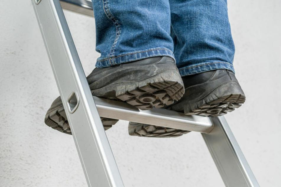 Ein Mann steht auf einer Leiter. (Symbolfoto)