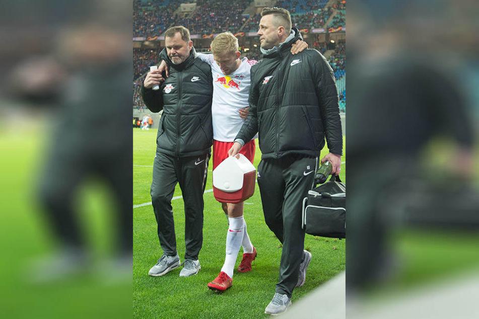 Mannschaftsarzt Frank Striegler (l.) und Physiotherapeut Alexander Sekora (r.) begleiten Konrad Laimer stützend nach draußen. Der Rechtsverteidiger hat sich einen Muskelriss im Oberschenkel zugezogen.