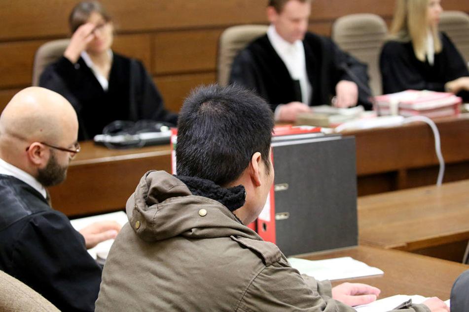 Der Angeklagte (r.) sitzt im Gerichtssaal neben seinem Anwalt.