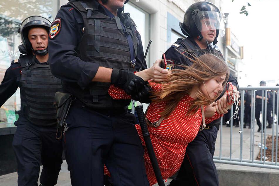 Polizisten führen eine Frau während der Protestaktion in Moskau ab.
