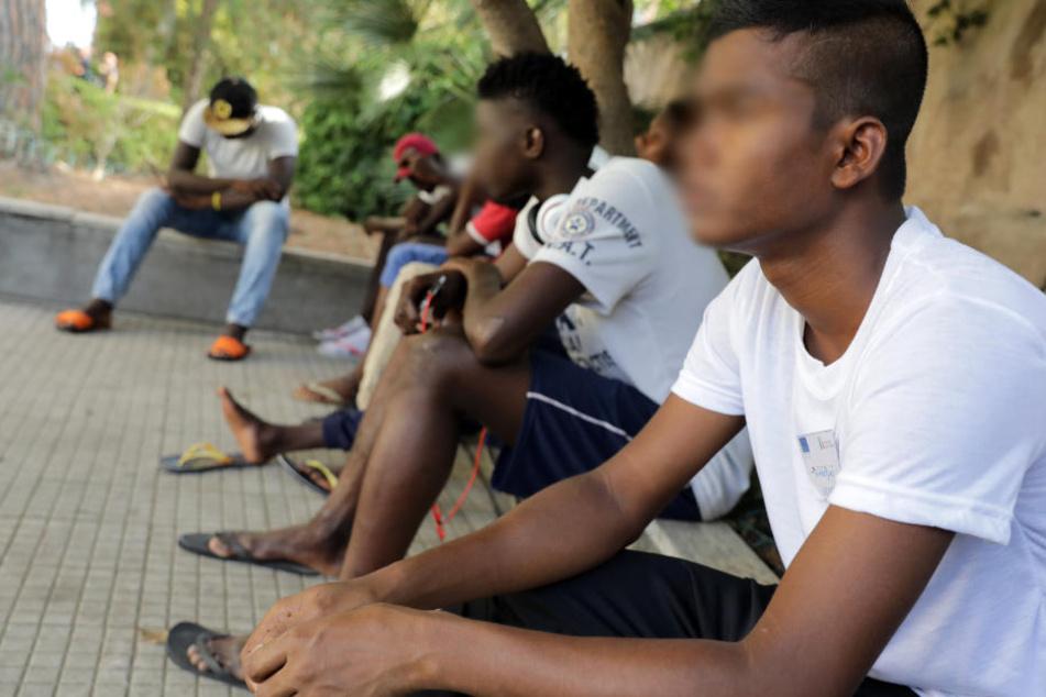 Junge Männer sitzen vor ihrem Flüchtlingsheim. Des Öfteren wird die Polizei auf Drogengeschäfte aufmerksam. (Symbolbild)
