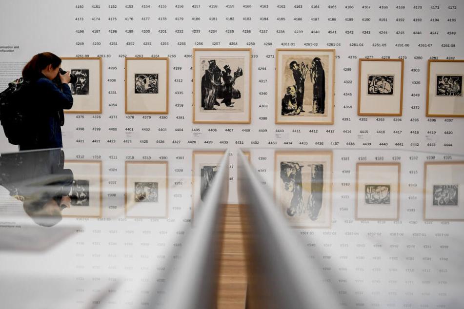 """Eine junge Frau fotografiert in der Berliner Ausstellung """"Emil Nolde - Eine deutsche Legende. Der Künstler im Nationalsozialismus""""."""