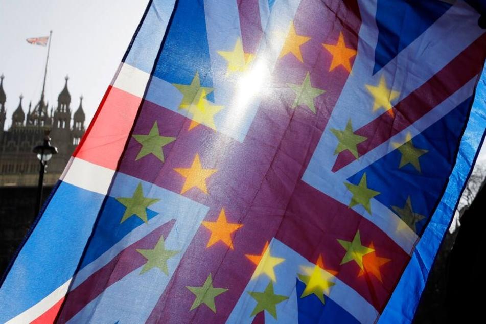 Ein Anti-Brexit-Aktivist schwenkt vor dem Parlament die Flaggen der Europäischen Union und Großbritanniens. (Archivbild)