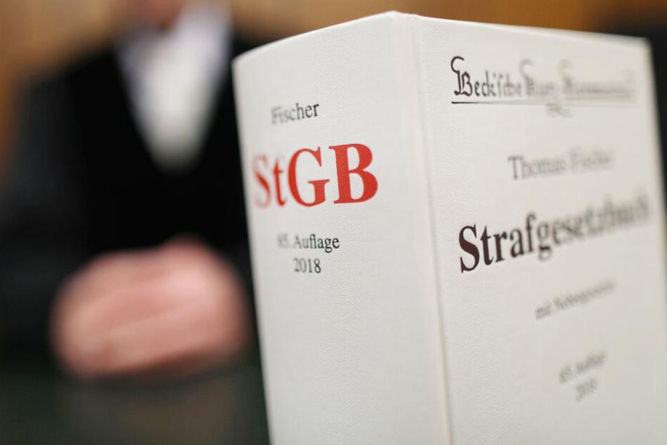 Ein Strafgesetzbuch (StGB) steht im Oberlandesgericht auf der Richterbank. In Hamburg begann am Mittwoch der Prozess gegen einen 29-Jährigen wegen Mordes, versuchten Mordes und schwerer Brandstiftung.