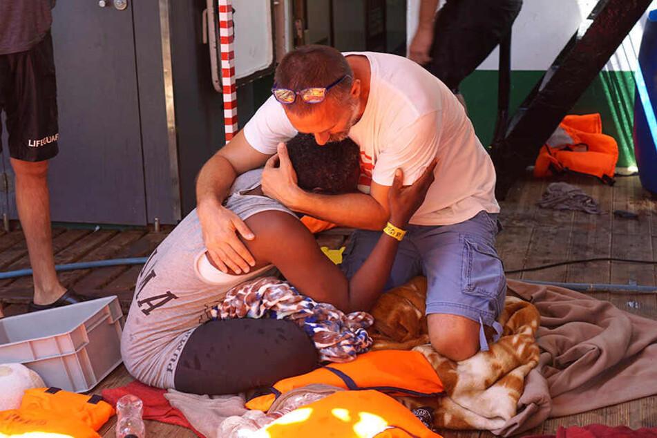 """Ein Besatzungsmitglied des spanischen Rettungsschiffes """"Open Arms"""" tröstet einen Migranten. Die dramatische Lage auf dem spanischen Rettungsschiff ist eskaliert."""