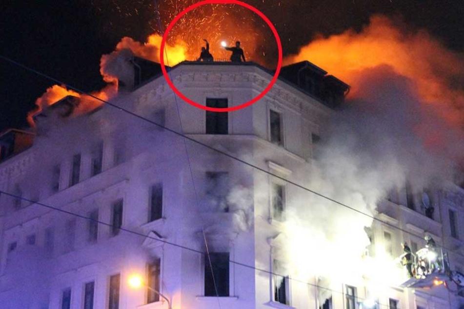 Zwei Bewohner versuchen auf dem Dach, mit ihrem Handy auf sich aufmerksam zu machen.