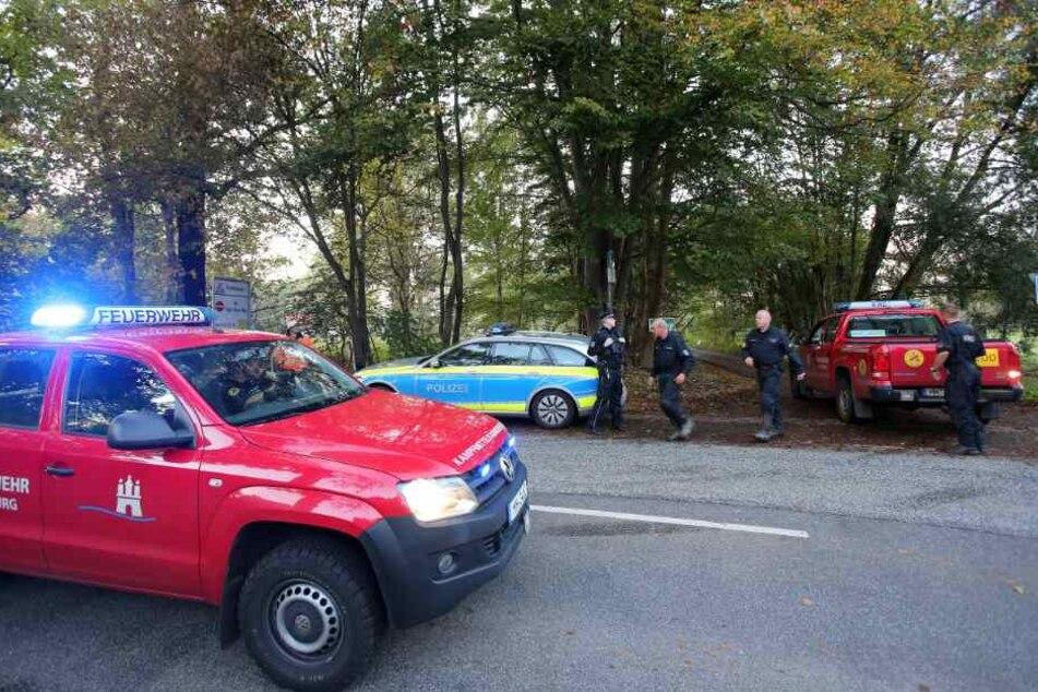 Einsatzkräfte stehen an der Zufahrt zu einem Gebiet, in dem eine Weltkriegsbombe gefunden wurde.