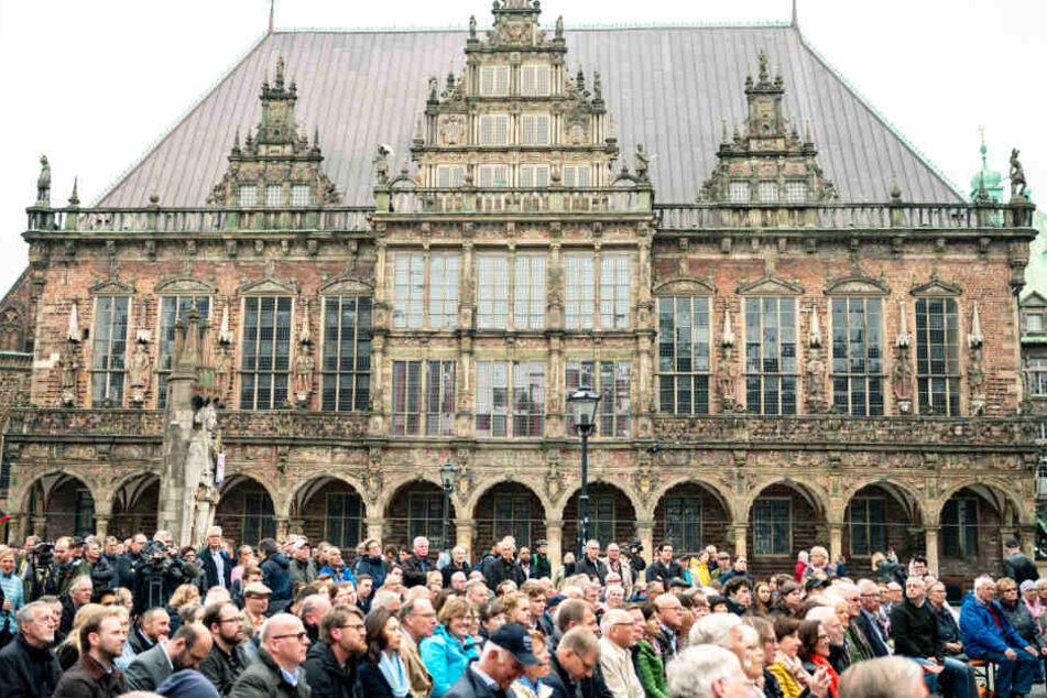 Bei der Wahlkampfveranstaltung der CDU sitzen viele Menschen auf dem Marktplatz vor dem alten Rathaus in Bremen.