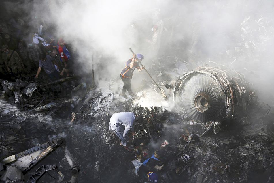 Freiwillige Helfer und Einsatzkräfte suchen nach Überlebenden, nachdem Flug PK8303 in einem Wohngebiet abgestürzt ist.