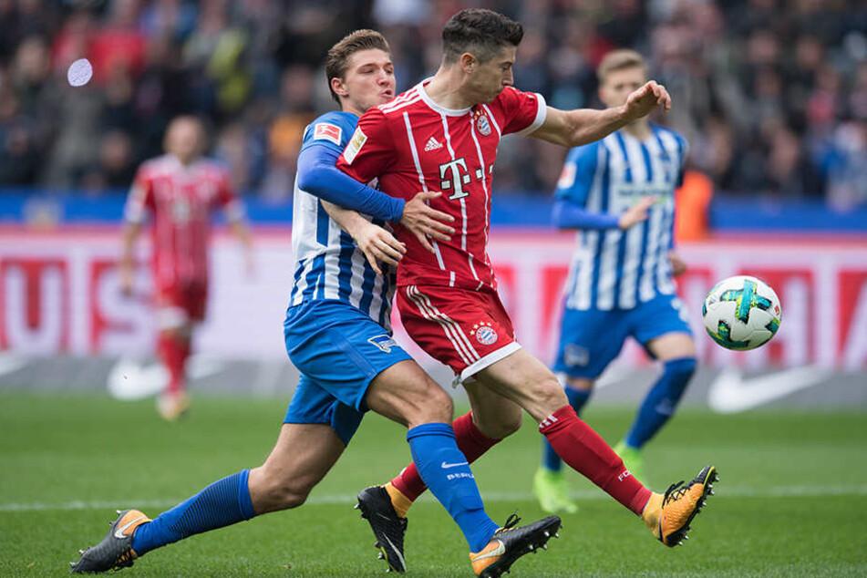 Berlins Niklas Stark (l) kämpft um den Ball gegen Bayerns Robert Lewandowski.